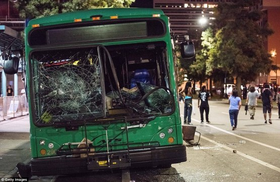 38ae9e0b00000578-3802230-demonstrators_walk_near_a_damaged_bus_the_north_carolina_governo-m-11_1474555793085